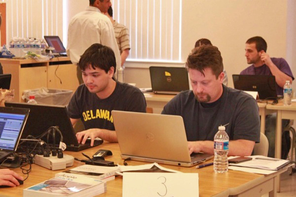 UD's Billy Bednar (left) at work during the 2013 U.S. Cyber Challenge