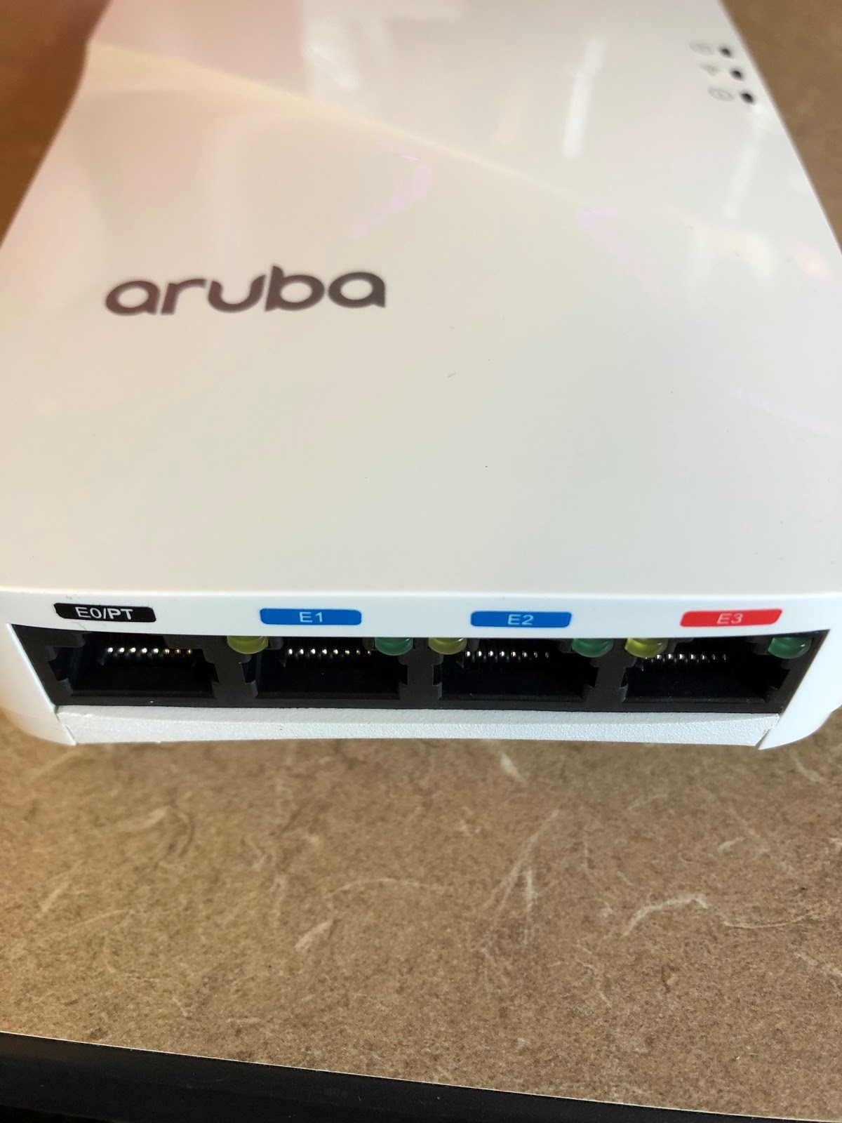 Aruba Wi-Fi access point from University Courtyard Apartments. Ports from left to right are: E0/PT (black), E1, E2 (blue), and E3 (red)